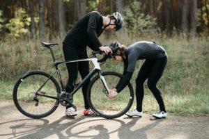 2 mannen zijn een mountainbike aan het repareren